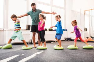 Happy children having fun while walking on Pilates balls on sports training in a health club. Male coach is with them.